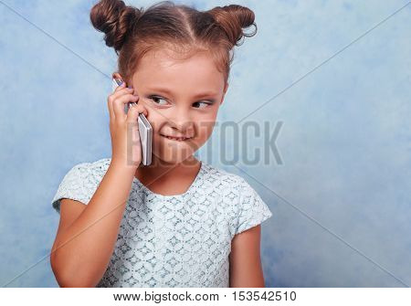 Funny Kid Girl Talking On Mobile Phone With Happy Smile On Blue Background With Empty Copy Space
