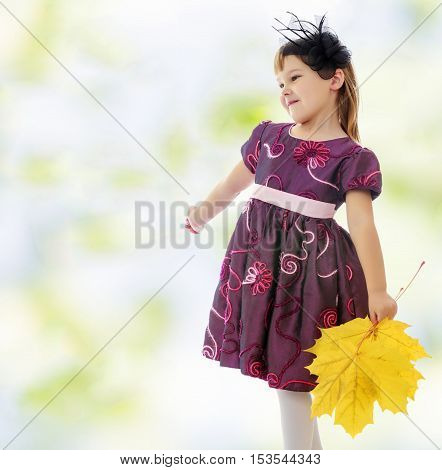 The concept of changing seasons in the life of a child. Caucasian little girl dressed in brown dress. She is holding a bouquet of maple leaves. Turning sideways to the camera.