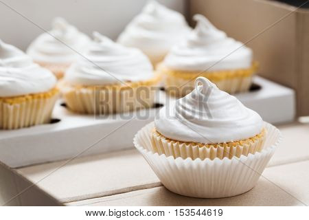 Cupcake packaging, delivery box, vanilla cupcakes with white cream, selective focus, close up