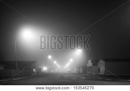 Main street of a small town shrouded in fog under street lights