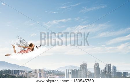 Young woman with megaphone flying high in sky