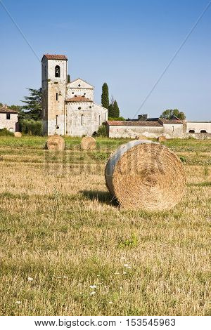Typical Tuscany Romanesque church surrounded by a field of wheat near a Cemetery. Tone Mapping Image