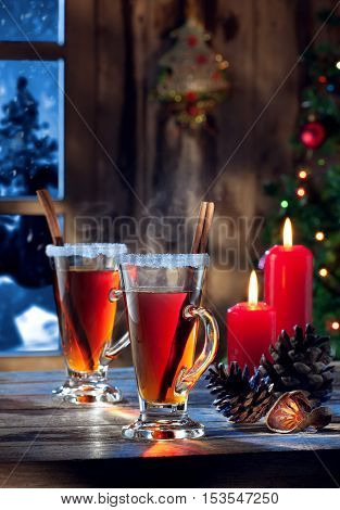 close up view  of two glasses with mulled wine on color back