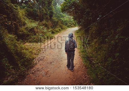 Young boy with a backpack walks on a jungle road