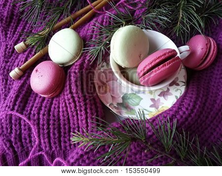 Macaroons in pretty colors on pink knitted garment