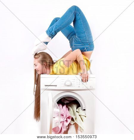 The young beautiful girl with long hair sitting on the bridge did the washing machine. Advertisement washing machine