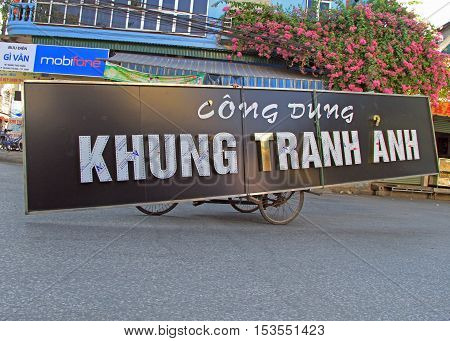 Vinh, Vietnam - May 29, 2015: unidentified man is carrying long signboard by tricycle in Vihn, Vietnam