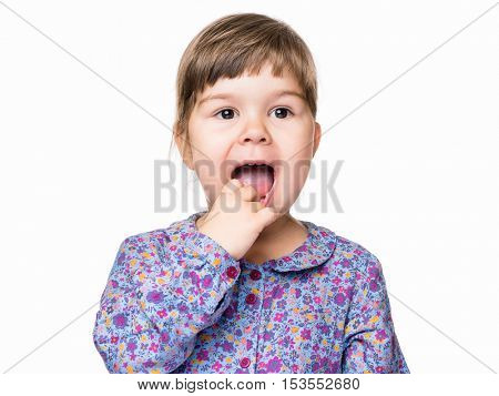 Emotional portrait of a 3 years old girl, with finger in her mouth. Cute caucasian baby isolated on white background. Beautiful preschool child posing in studio. Healthy carefree kid playing indoors.