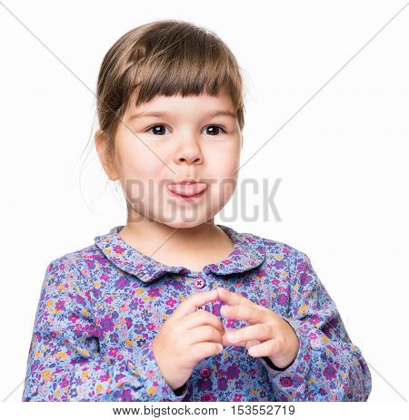 Emotional portrait of a 3 years old girl, shows tongue. Cute caucasian baby isolated on white background. Beautiful preschool child posing in studio. Healthy carefree kid playing indoors.