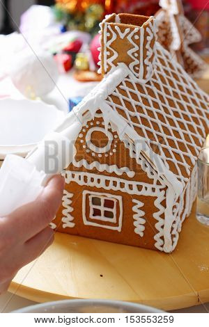 Making of christmas gingerbread house. Roof decorating. Close up view with selective focus.
