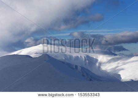 Blue sky with beautiful cumulus clouds over a mountain ridge. Winter landscape on a sunny day. Carpathians, Ukraine, Europe