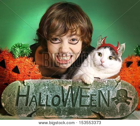 preteen handsome boy with cat in halloween pumpkin decorations with make up