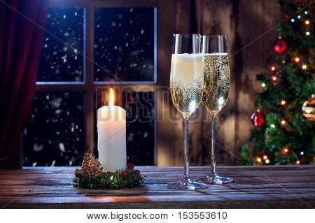 close up view of two glasses with champagne and candle on color back