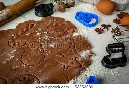 Making traditional christmas gingerbread cookies. Christmas-tree branches, a rolling pin, whisk for whipping eggs, nuts and cones they lie on a table nearby