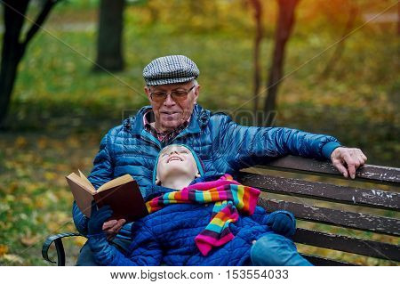 Grandson with grandfather in the autumn Park reading a book