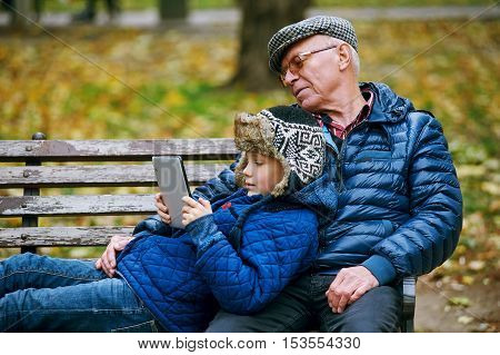 Grandson with grandfather in the autumn Park and read using a tablet