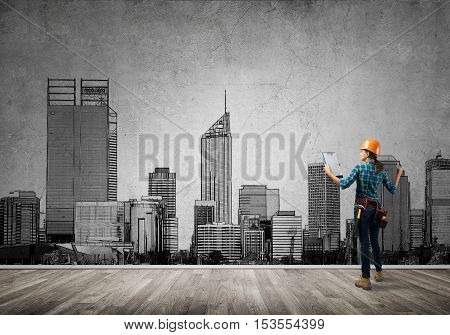 Back view of engineer woman with folder and sketches of construction project on wall