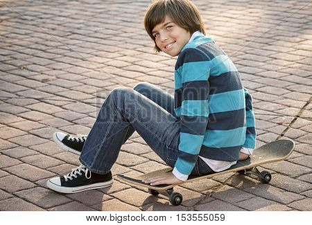 Happy young boy sitting on his skateboard cobblestone pavement