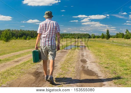 Mature man wearing blinders shirt and hat walking on a summer country road with green suitcase