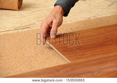 builder puts a cork laminate substrate on the bottom of the wood board