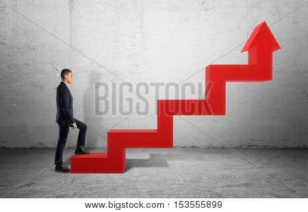 A businessman in profile walking up a big red arrow in form of a ladder on the background of a grey wall. Business and management. Ladder of success. Reaching aims.