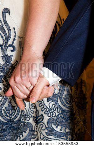 tightly holding hands young men in elegant clothes