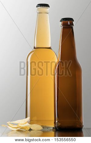 Large and small closed beer bottles with lying next pile of chips on a gray background