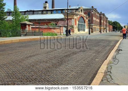 Kronstadt Russia - 10 July 2016: Cast iron paving on Penkovy bridge (was built in 1860) and Machine school of the Baltic fleet (opened in 1868) in Kronstadt.