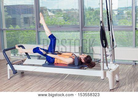 Pilates reformer workout exercises woman brunette at gym indoor.