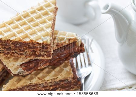 Stack of wafer sheets filled with caramelized sugar and hazelnut cream served on white plate