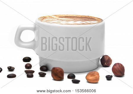 white cup of coffee with cream on a white background decorated with coffee beans and nuts