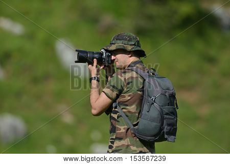 Landscape professional photographer taking a picture in nature with green blurry background