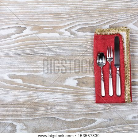 Overhead view of a festive cloth napkin with dinner set silverware.