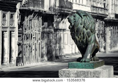 Black and white street scene of Old Havana with the symbolic bronze lion statue at El Prado avenue in its original color
