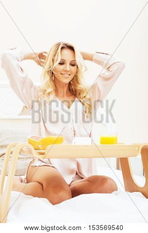 young beauty blond woman having breakfast in bed early sunny morning, princess house interior room, healthy lifestyle concept close up