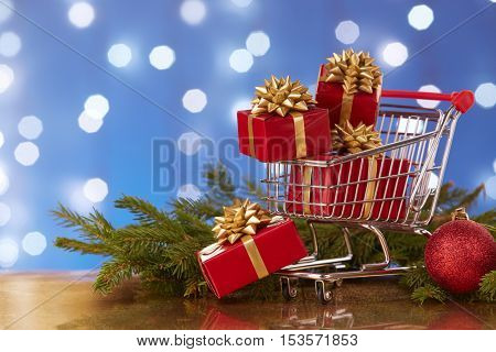 Shopping trolley with gift boxes and brenches of fir-tree with decoration on a blue background with light of garland. Christmas and New Year sale.