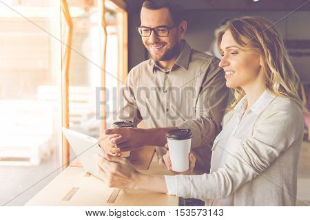 Handsome businessman and beautiful business lady are using a digital tablet drinking coffee and smiling while co-working
