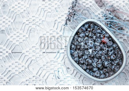 Fresh blueberries in a gray bowl against the background of dried flowers and openwork tablecloth. Space for copy selective focus.