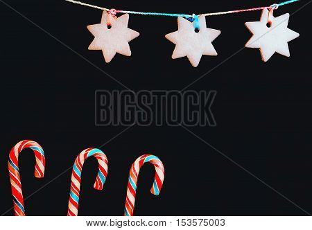 Lollipops candy canes and a hanging ginger biscuits in the shape of a star on a black backdrop. Greeting card holiday background with space for copy.