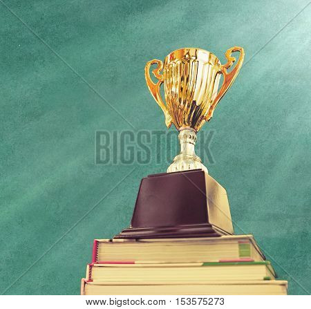 trophy on top stack of book .