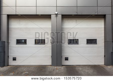 Two white garage doors. Sectional lift gates.
