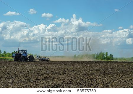 Agricultural Landscape - Tractor working on the field - spring sunny day