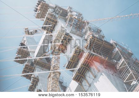 Multiple scaffolding construction crane on a modern rope bridge under construction in Rio de Janeiro on a bright summer day