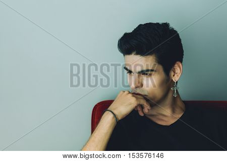 Attractive modern young brazilian white male with black hair and cross-earring is sitting deep in thoughts and reflective