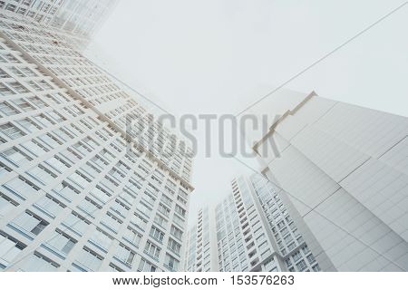 White contemporary residential skyscraper apartment building in Moscow on a cloudy day two housing body regular windows view from bottom