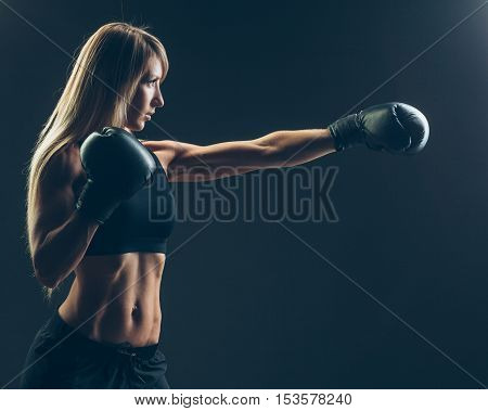beautiful woman with the red boxing gloves, black background.