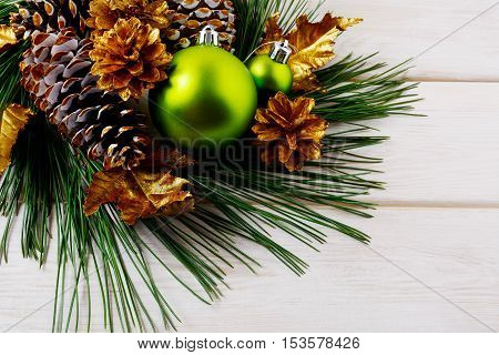 Christmas background with green ornaments and golden pine cones. Christmas party decoration.