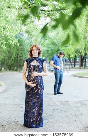Funny image. Happy pregnant woman with husband standing together in foliage. Pregnancy in long dress. Future daddy in jeans and blue shirt.