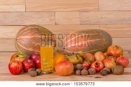 Autumn nature fruits concept. Fall fruits and orange juice, on a wooden table, studio picture