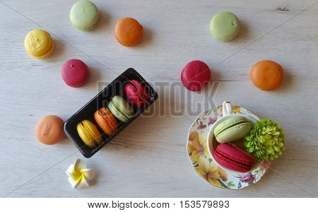 Macaroons in pretty colors on a white wooden background